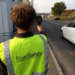Community member using a hand held speed detection gun