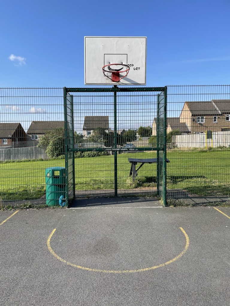 Basketball hoop above a football goal in the multi use games area. A rubbish bin and picnic bench are in the background surrounded by green grass.